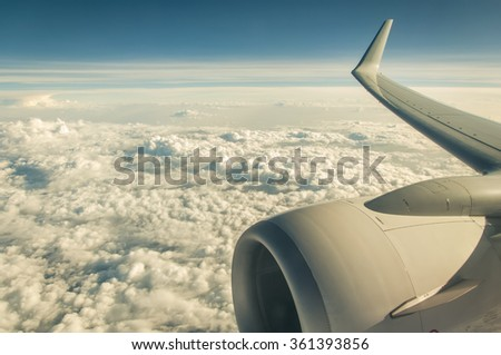 Airplane wing and jet's engine in the sky - stock photo