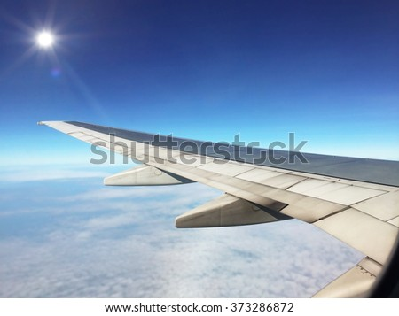 Airplane wing fly above clouds on sunlight