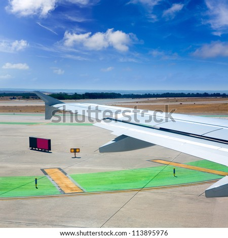 Airplane wing leaving the airport with airstrip road signs - stock photo