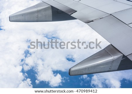 Airplane wing with cloud and sky in background