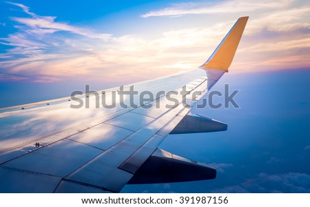 Airplane wing with sunrise in light flare - stock photo