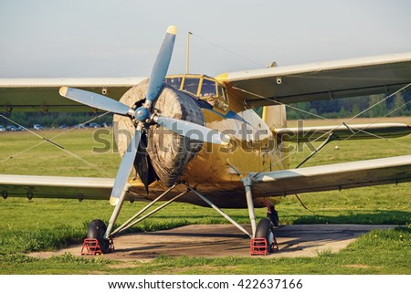 Airplane with propeller. Old retro plane close-up. Vintage biplane. Front view, with the side of the fuselage. Propeller, engine and cockpit. - stock photo