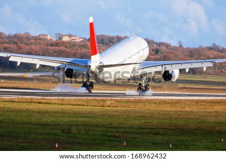 Airplane with two engines landing on runway back view - touchdown with tire smoke  - stock photo