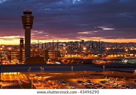 Airport at sunset with lit city skyline. - stock photo