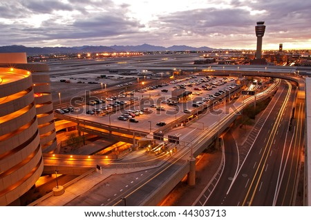 Airport at sunset with lit city skyline.