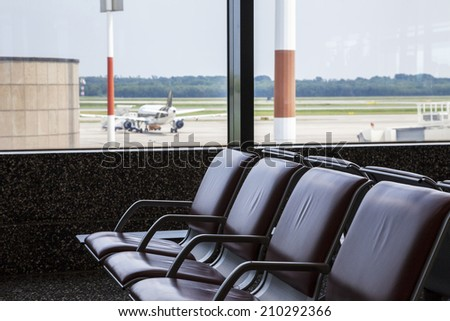 Airport benches with an airplane in the background  - stock photo