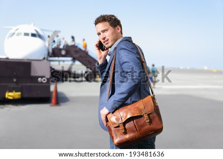 Airport business man on smartphone by plane. Young male professional hip businessman talking on smartphone boarding airplane going flying on business trip. Casual male wearing suit and laptop bag. - stock photo