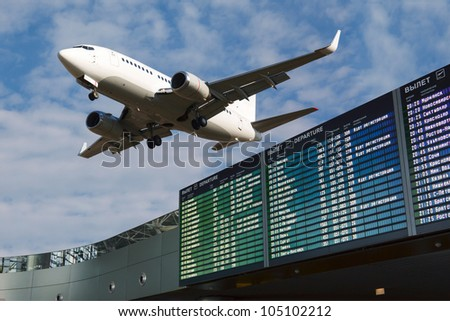 Airport flight schedule with list of flights and civil airliner on blue sky - stock photo