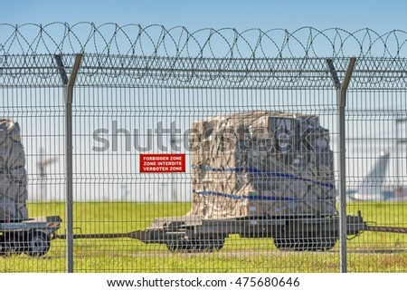 Airport perimeter fence with forbidden zone warning sign cargo loader platform trolley delivering bulk cargo load to cargo aircraft fin tail silhouette background detail exterior landscape warm view