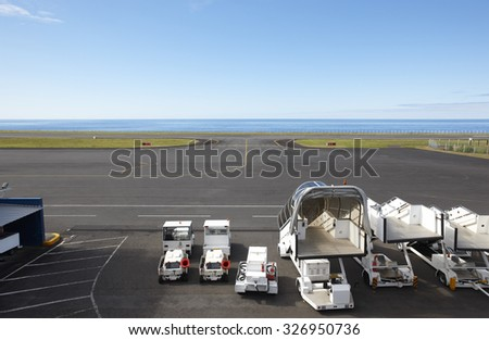 Airport runway close to the ocean with auxiliar vehicles. Horizontal