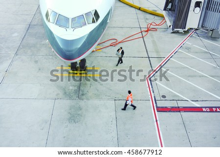 Airport scene. A docked airplane gets refueled and recharged.