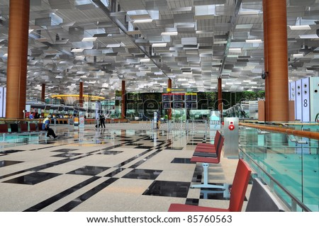 Airport scene of Terminal 3 of Changi Airport in Singapore - Travellers relaxing and waiting for check-in - stock photo