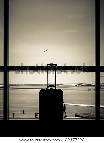 Airport scene with unattended suitcase in lounge, jet flying and parked - stock photo