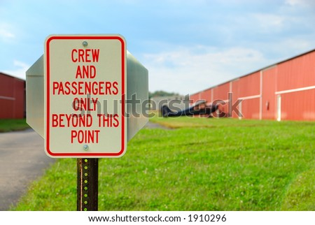 Airport Sign - Crew And Passengers Only Beyond This Point - a security  sign at a small airport at the entrance road to the plane and hangar. - stock photo