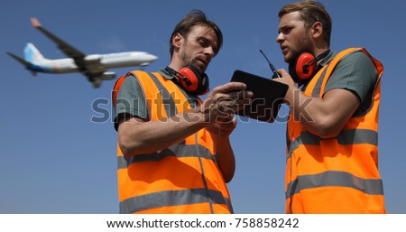 Airport Team Activity, Men Work on Digital Tablet, Talk on Walkie Talkie Collaborating with Air Traffic Control Tower, Airplane Flying Over Aircrew Controllers Ground Crew, Aircraft Passing Overhead