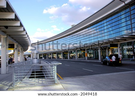 Airport terminal with cars outside and bright blue sky - stock photo