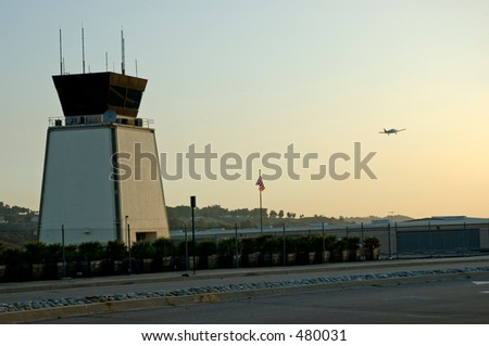 Airport traffic control tower at sunset with small airplane taking off - stock photo