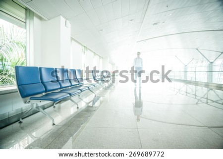 Airport waiting area with rows of blue seats and a blurred figure of a lonely passenger. - stock photo