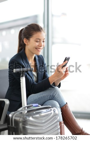 Airport woman on smart phone at gate waiting in terminal. Air travel concept with young casual business woman sitting with carry-on hand luggage trolley. Beautiful young mixed race female professional - stock photo