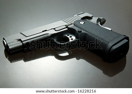 airsoft pistol on reflective surface