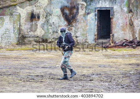 Airsoft player holding position in ruins - stock photo
