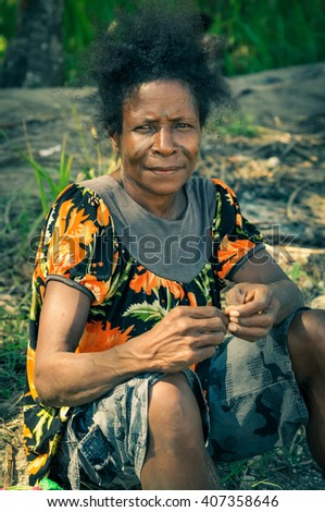Aitape, Papua New Guinea - July 2015: Native woman with black hair dressed in colourful shirt sits on ground and looks to photocamera in Aitape, Papua New Guinea. Documentary editorial.