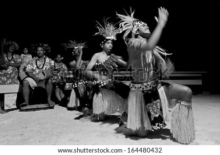 AITUTAKI - SEP 19:Polynesian Pacific Island Tahitian male dancers in costume dancing on Sept 19 2013 on tropical beach in Aitutaki lagoon Cook Islands. (BW)  - stock photo