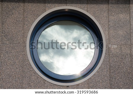 Ajar round window on the tiled granite wall - part of the urban architecture. - stock photo