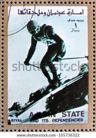 AJMAN - CIRCA 1973: a stamp printed in the Ajman shows Downhill Skiing, Alpine Skiing, Winter Olympics, circa 1973 - stock photo