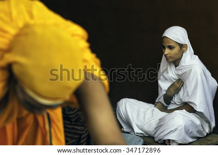 AJMER, INDIA - OCTOBER 26, 2011: A Digambara Jain nun waits patiently for food during Chaturmas festival at the Jain temple on October 26, 2011 in Ajmer, Rajasthan, India.