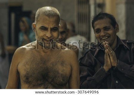 AJMER, INDIA - OCTOBER 26, 2011: Jain devotee seeks blessing from nude senior Digambara Jain Monk during the festival of Chaturmas at Jain temple on October 26, 2011, Ajmer, Rajasthan, India.