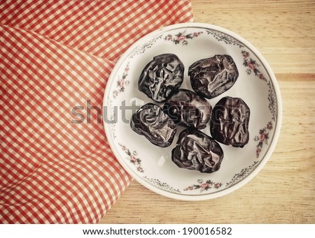 Ajwa Dates fruit in retro style (Ajwa is a soft dry variety of date fruit from Saudi Arabia. It is cultivated at the city of Madinah) - stock photo