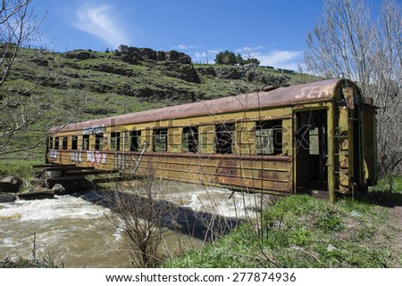 AKHALKALAKI, GEORGIA - MAY 06, 2015: Old railway carriage as a bridge across mountain river - stock photo