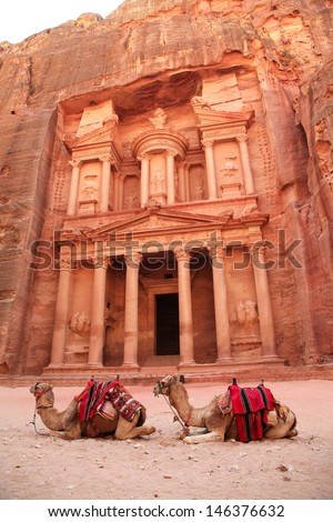 Al Khazneh in the ancient Jordanian city of Petra, Jordan. It is known as The Treasury. Petra has led to its designation as a UNESCO World Heritage Site and two camels are sitting behind the door - stock photo