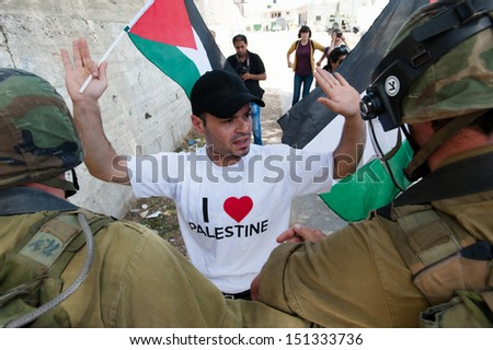AL MA'SARA, PALESTINIAN TERRITORY - MAY 24: Palestinian activists confront Israeli soldiers during a protest against the occupation and separation wall in the West Bank town Al Ma'sara, May 24, 2013. - stock photo