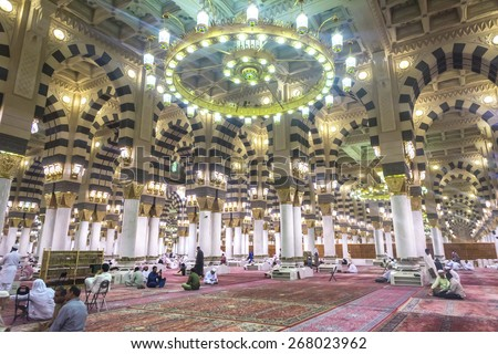 AL MADINAH, KINGDOM OF SAUDI ARABIA - MAR 07: Muslim pray and read Quran inside Masjid (mosque) Nabawi on March 07, 2015 in Al Madinah, S. Arabia. Nabawi mosque is the 2nd holiest mosque in Islam. - stock photo