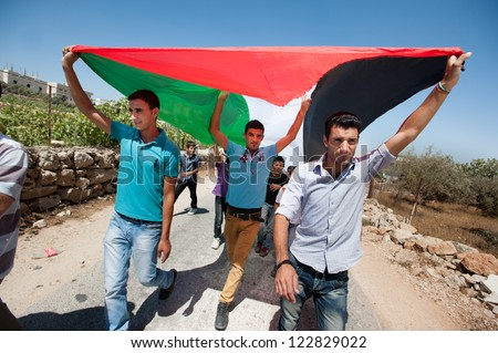AL MASARA, PALESTINIAN TERRITORY - SEPTEMBER 14: Palestinians march with a large flag during a weekly nonviolent demonstration against the separation wall, Al Ma'sara, West Bank, September 14, 2012. - stock photo