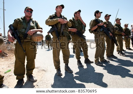 AL-WALAJA, OCCUPIED PALESTINIAN TERRITORIES - AUGUST 27:  Israeli soldiers block the street during a protest by Israeli and Palestinian activists in the West Bank town of Al-Walaja, Occupied Palestinian Territories on August 27, 2011. - stock photo