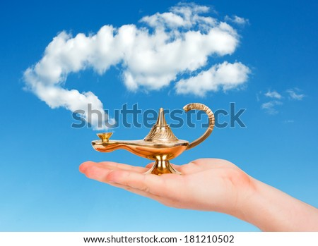 Aladdin lamp in human hand against cloudy sky - stock photo