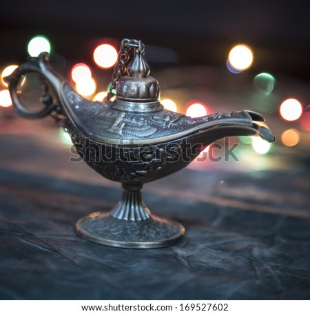 Aladdin Lamp on grey textile in front of bokeh lights - stock photo