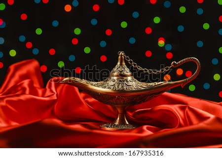 Aladdin Lamp on red textile in front of unfocused lights - stock photo