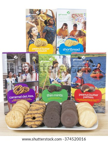 ALAMEDA, CA - FEBRUARY 09, 2016: Boxes of the five original Girl Scout cookies produced by ABC Bakers, with all cookie varieties on a plate in front of the boxes on light wood table