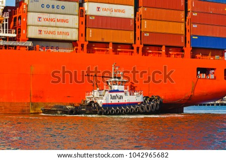 "Alameda, CA - March 9, 2015: Oakland Oakland Container Shipyard, San Francisco Bay, the AmNAv tug ""Liberty"" is maneuvering the Hamburg Sud ship ""Santa Barbara"" into dock"
