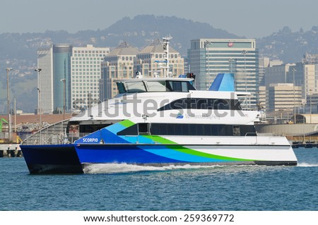 "Alameda, CA - March 9, 2015: Oakland  San Francisco Bay Ferry ""SCORPIO"" leaving Oakland towards San Francisco, with the cityscape of Oakland behind"