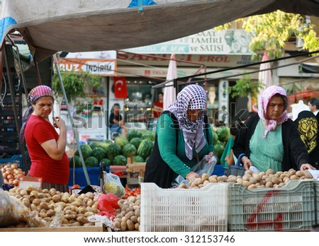 ALANYA, TURKEY - August 28, 2015: Imported temporary market in the city centre of Alanya. Several local women are choosing potatoes scattered on the counter.