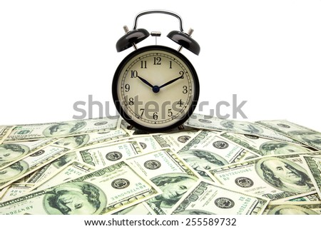 alarm clock and banknotes of one hundred dollars