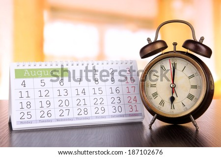 Alarm clock  and calendar on bright background - stock photo