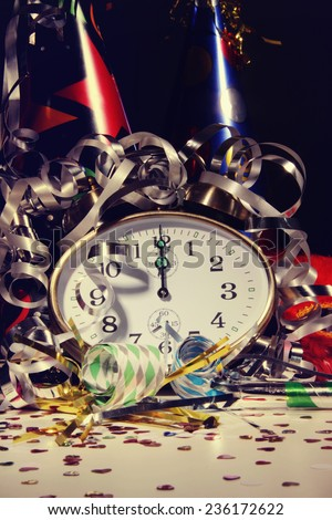 Alarm clock and decorations on table with festive background - stock photo
