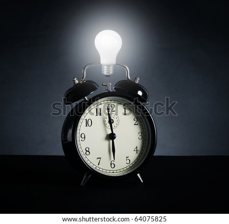 Alarm clock and electric lamp. A symbol of time, new idea and success. - stock photo