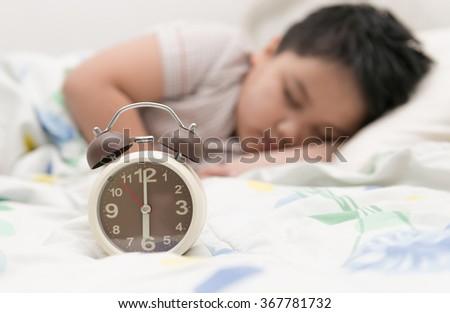 alarm clock and fat boy sleep on background - stock photo